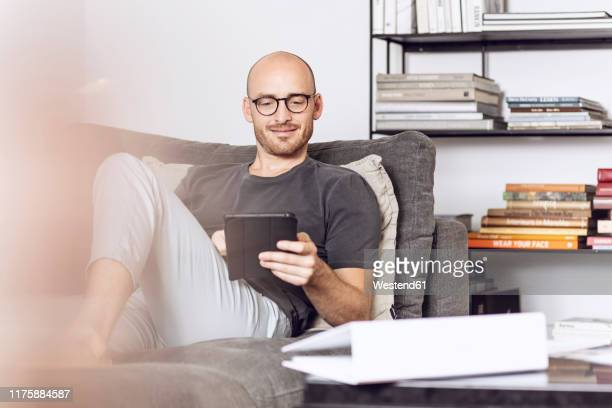 man sitting at home on a couch using digital tablet - foco diferencial imagens e fotografias de stock