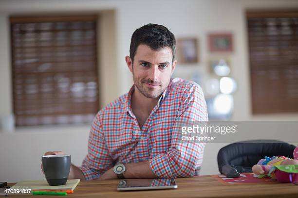 man sitting at kitchen counter with cup of coffee and digital tablet - hommes d'âge moyen photos et images de collection