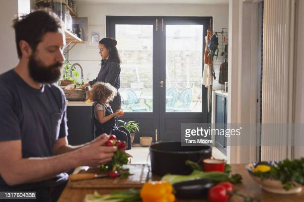 man sitting at kitchen table preparing vegetables with his family in the background. - crucifers stock pictures, royalty-free photos & images
