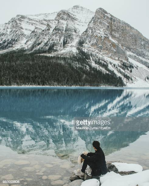 Man Sitting At Lake By Snowcapped Mountains During Winter