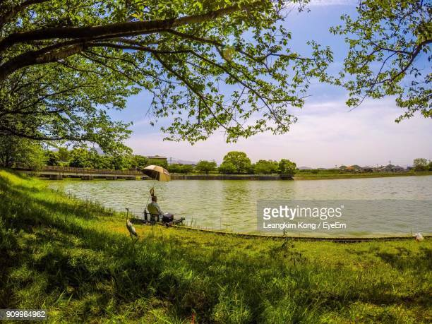 man sitting at lakeshore against sky - lakeshore stock pictures, royalty-free photos & images