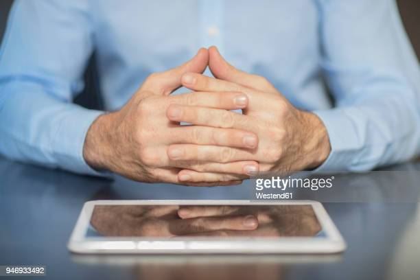 man sitting at office desk with tablet folding hands - mani incrociate foto e immagini stock