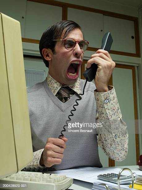 Man sitting at office desk yelling into telephone receiver, close-up