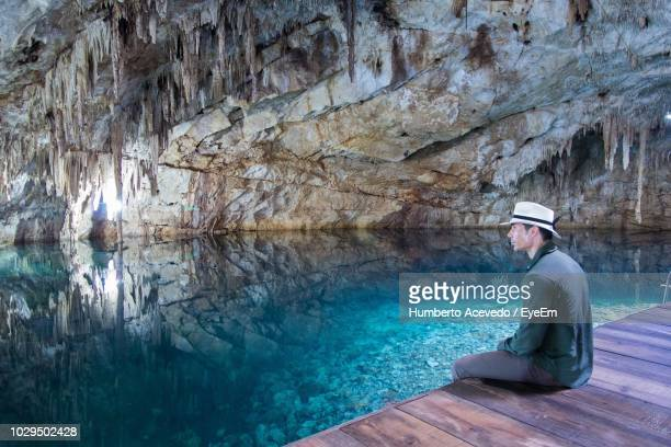 Man Sitting At Poolside In Cave