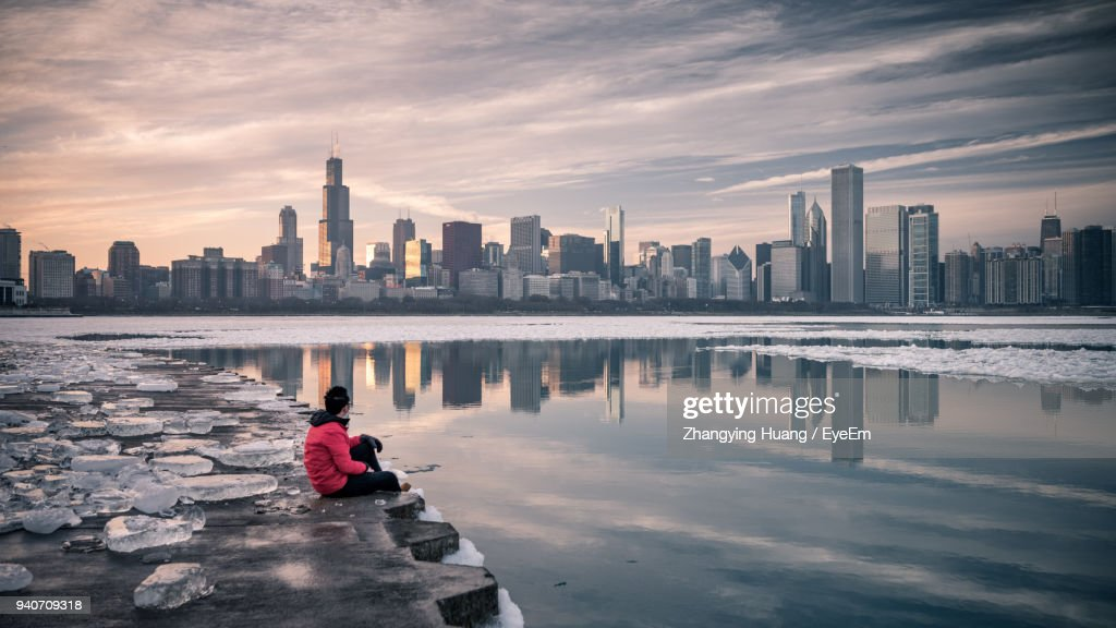 Man Sitting At Riverbank During Winter In City : Stock Photo