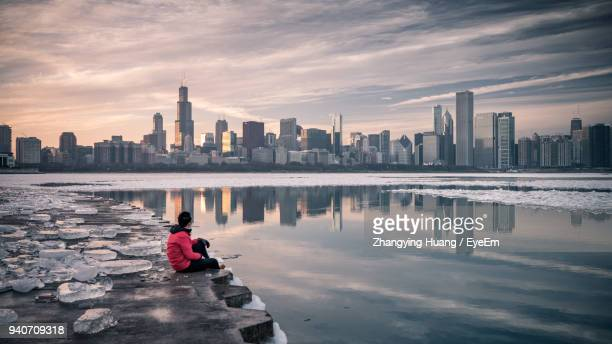 Man Sitting At Riverbank During Winter In City