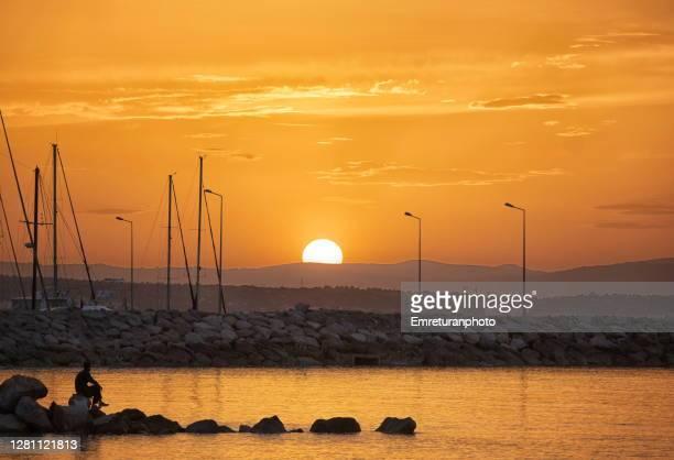 man sitting at sunset near ciftlikkoy marina onan autumn day. - emreturanphoto stock pictures, royalty-free photos & images