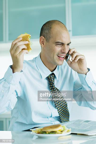 'Man sitting at table eating hamburgers, reading newspaper and using cell phone '