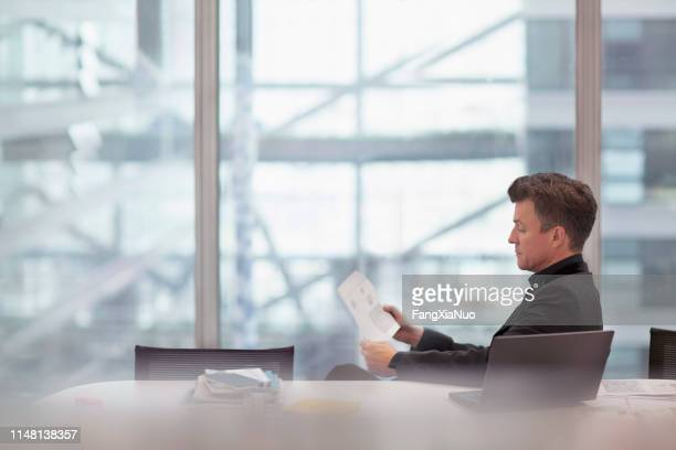 man sitting at table reading in meeting room - business finance and industry stock pictures, royalty-free photos & images