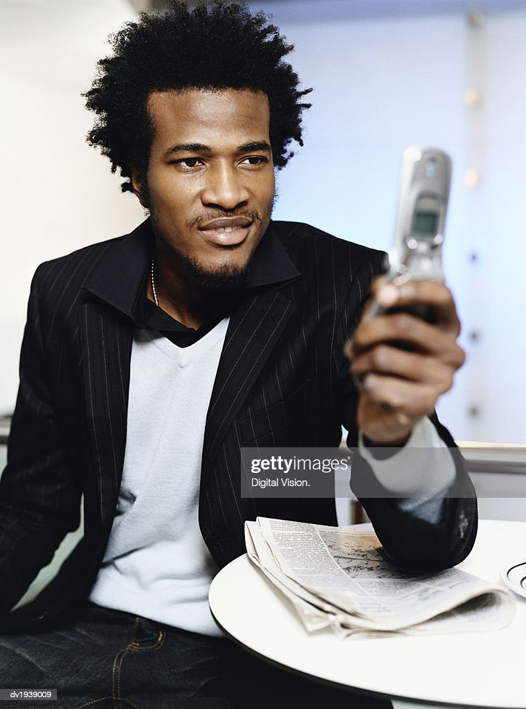 Man Sitting at Table Using His Mobile Phone : Stock Photo