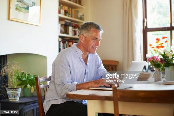 man sitting at table using laptop - richard drury stock pictures, royalty-free photos & images