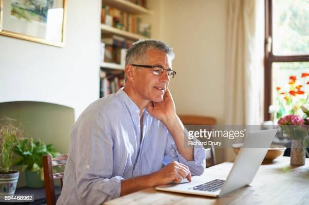 Man sitting at table using laptop