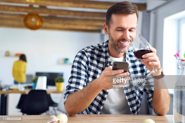 man sitting at table, using smartphone, relaxing with a glass of red wine - チェックシャツ ストックフォトと画像