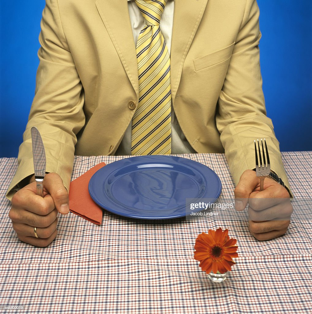 Man sitting at table with empty plate, holding cutlery : Stock Photo