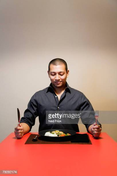 Man sitting at table with full plate of food