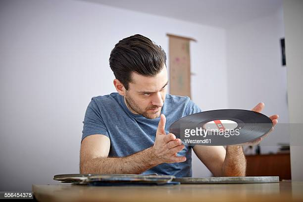Man sitting at table with old vinyl records