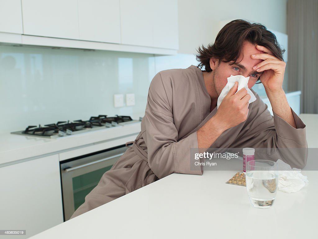Man sitting at table with tissue blowing nose and holding head : Stock Photo