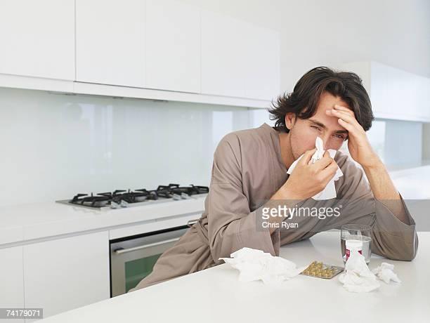 hombre sentado en la mesa con tejido sonarse y - flu virus fotografías e imágenes de stock