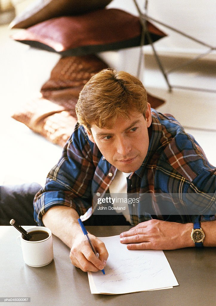 Man sitting at table, writing, high angle view : Stockfoto