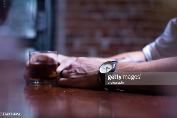 man sitting at the bar drinking a glass of whisky - alcoholismo fotografías e imágenes de stock