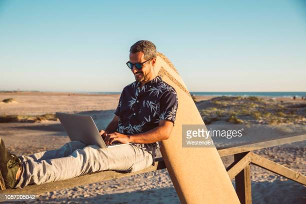 man sitting at the beach, using laptop, with surfboard leaning on fence - net sports equipment stock pictures, royalty-free photos & images