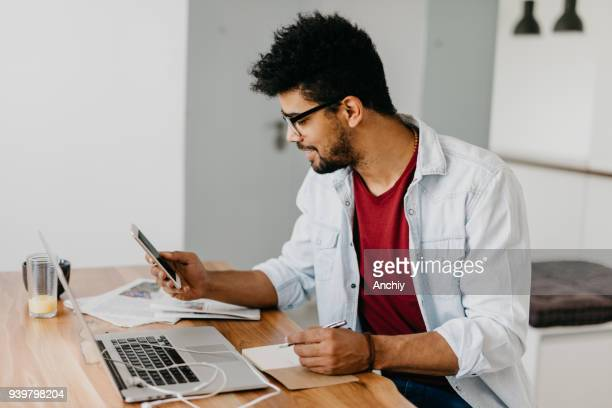 Man sitting at the desk and paying bills with his credit card online using laptop.