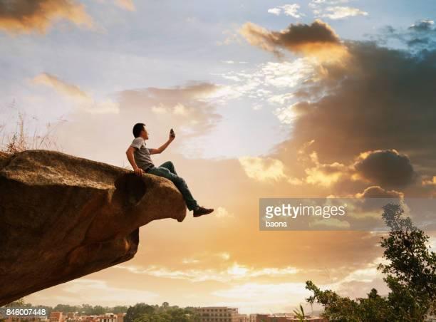 Mann sitzt am Rand einer Klippe mit Telefon