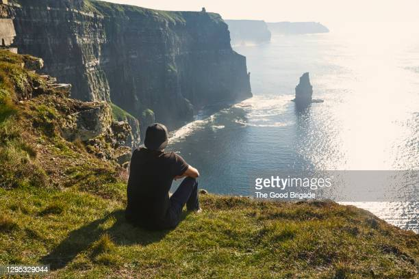 man sitting at the edge of  cliffs of moher, galway, ireland - ireland stock pictures, royalty-free photos & images