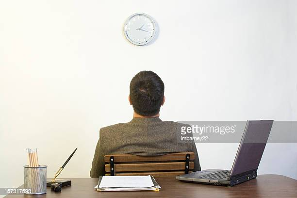 A man sitting backing against a desk looking up at a clock