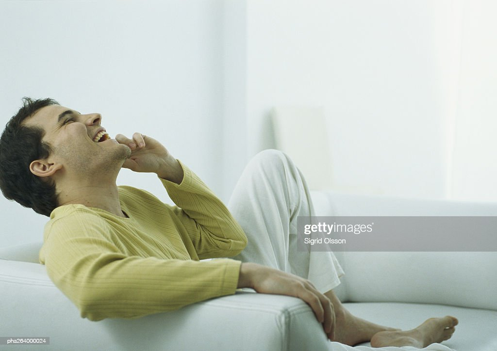 Man sitting barefoot on couch talking on phone, laughing with head back : Stockfoto