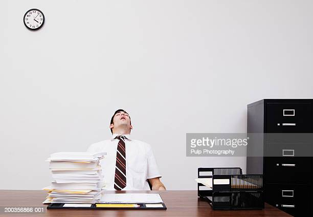 man sitting behind office desk, head back, mouth open, sleeping - 頭をそらす ストックフォトと画像