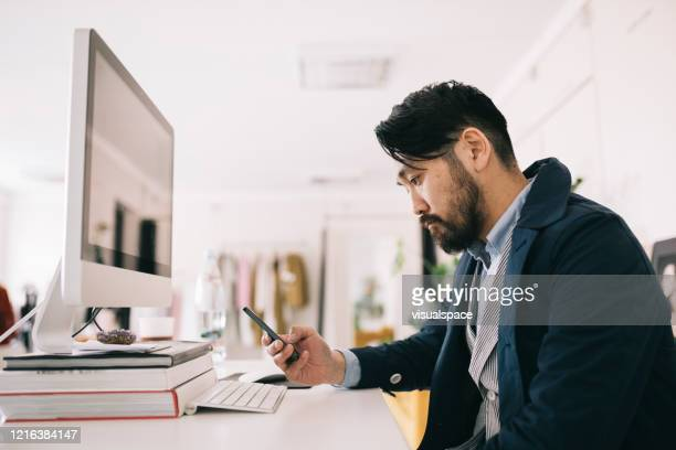 man sitting behind the desk, looking at smartphone - wasting time stock pictures, royalty-free photos & images