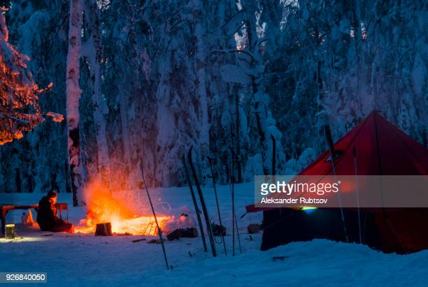 man sitting beside campfire, at night, near tent, in snow covered forest, russia - wilderness stock pictures, royalty-free photos & images