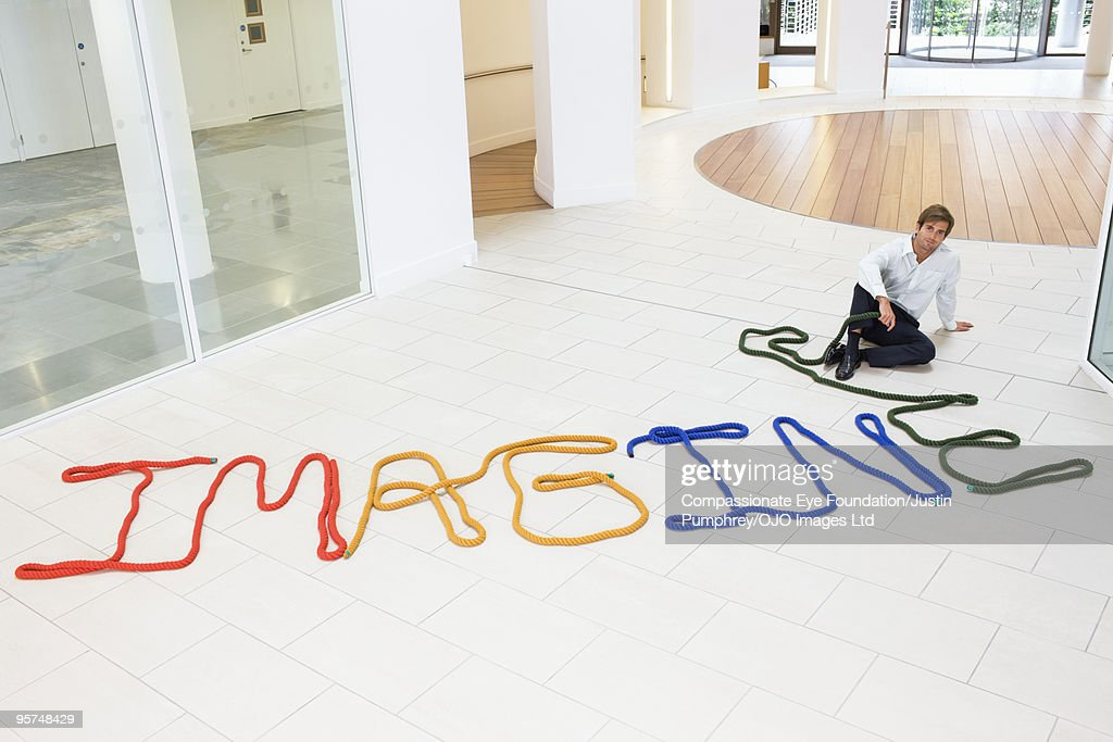 Man sitting beside the word imagine : Stock Photo