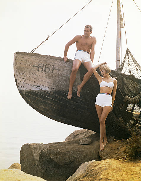 Man sitting boat, woman standing beside