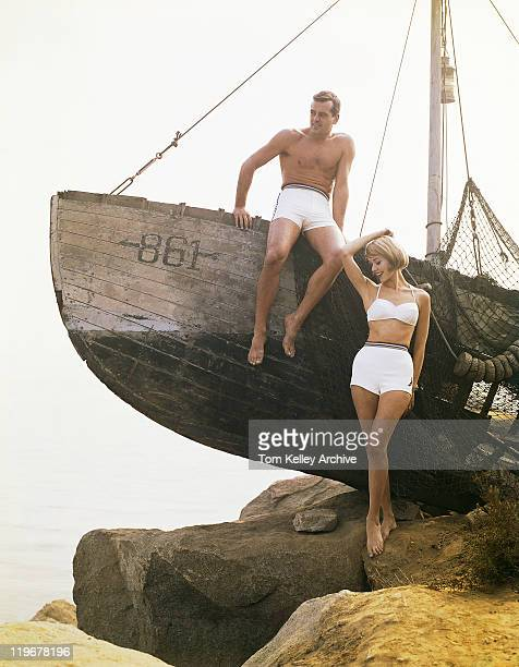man sitting boat, woman standing beside  - 1950 1959 stock photos and pictures