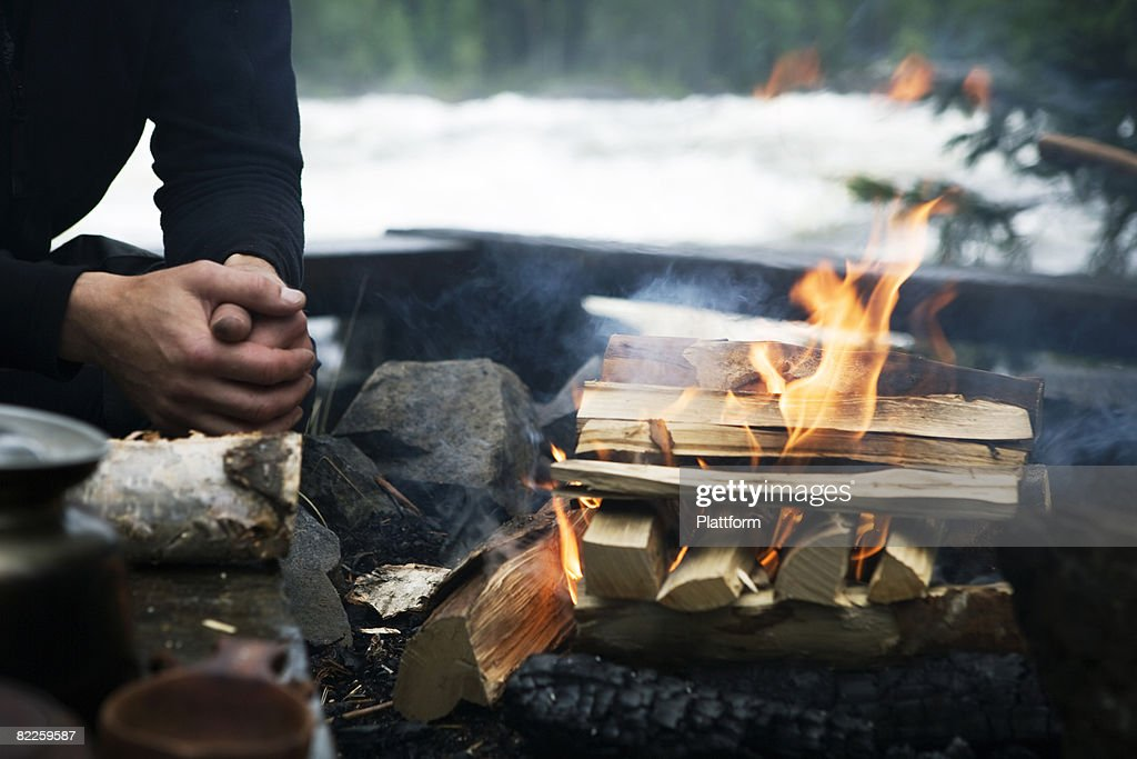 A man sitting by a camp fire Sweden. : Stock Photo