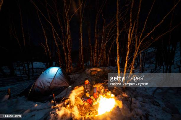 Man Sitting By Bonfire In Forest At Night