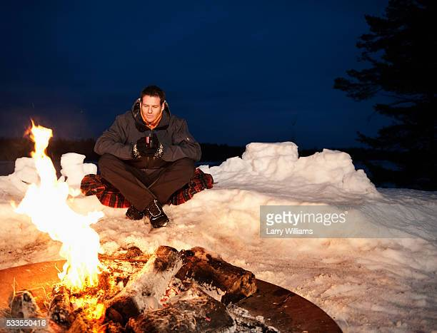 Man sitting by campfire