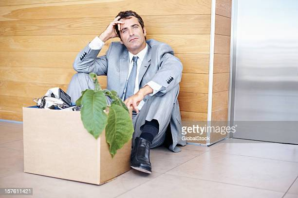 Man sitting by elevator with box of office stuff