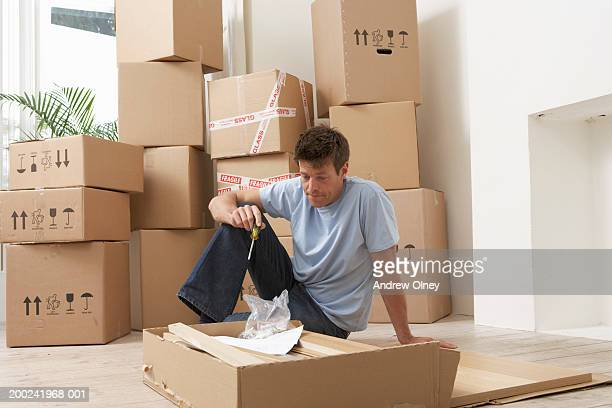 Man sitting by flat-pack furniture, removal boxes in background