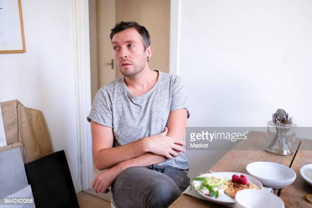 man sitting by food on table at home - mid adult men fotografías e imágenes de stock