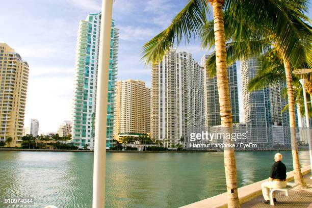 man sitting by lake on bench in city - fort lauderdale stock pictures, royalty-free photos & images