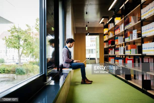 man sitting by large window working in library - post secondary education stock pictures, royalty-free photos & images