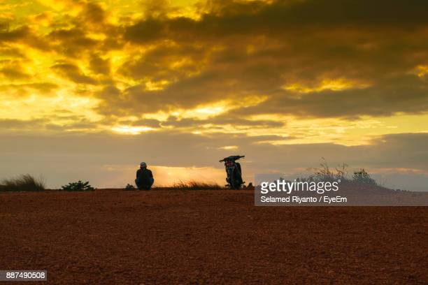 Man Sitting By Motorcycle On Field Against Sky During Sunset
