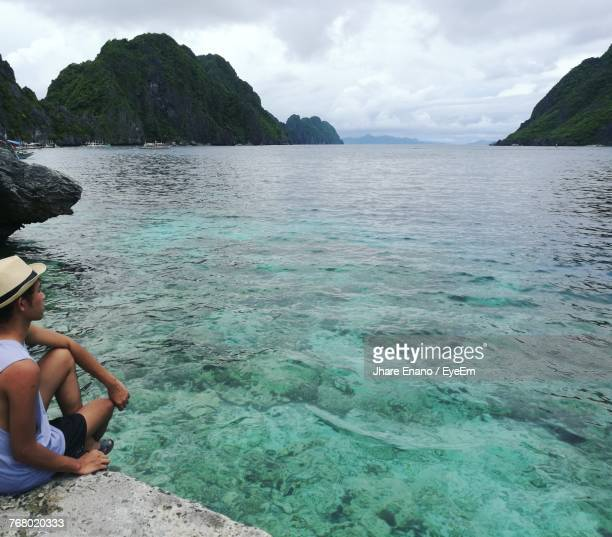 man sitting by sea against sky - enano stock pictures, royalty-free photos & images