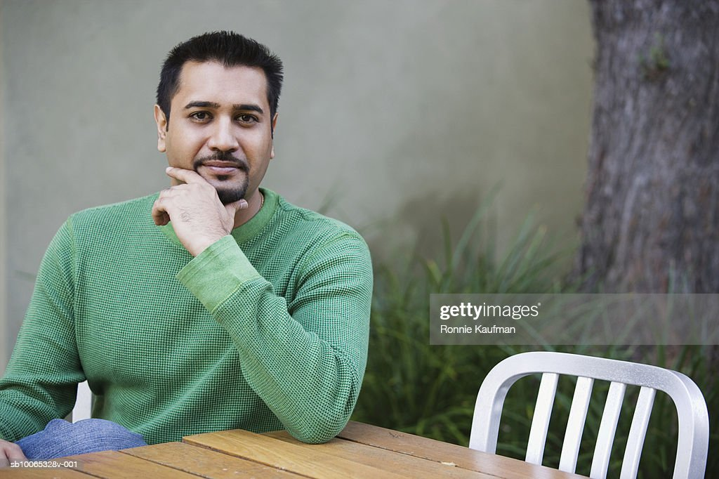 Man sitting by table, smiling, portrait : Foto stock
