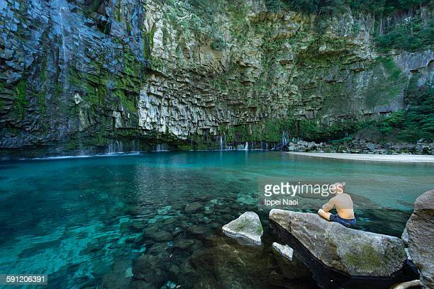 man sitting by waterfall lagoon, japan - ippei naoi stock photos and pictures