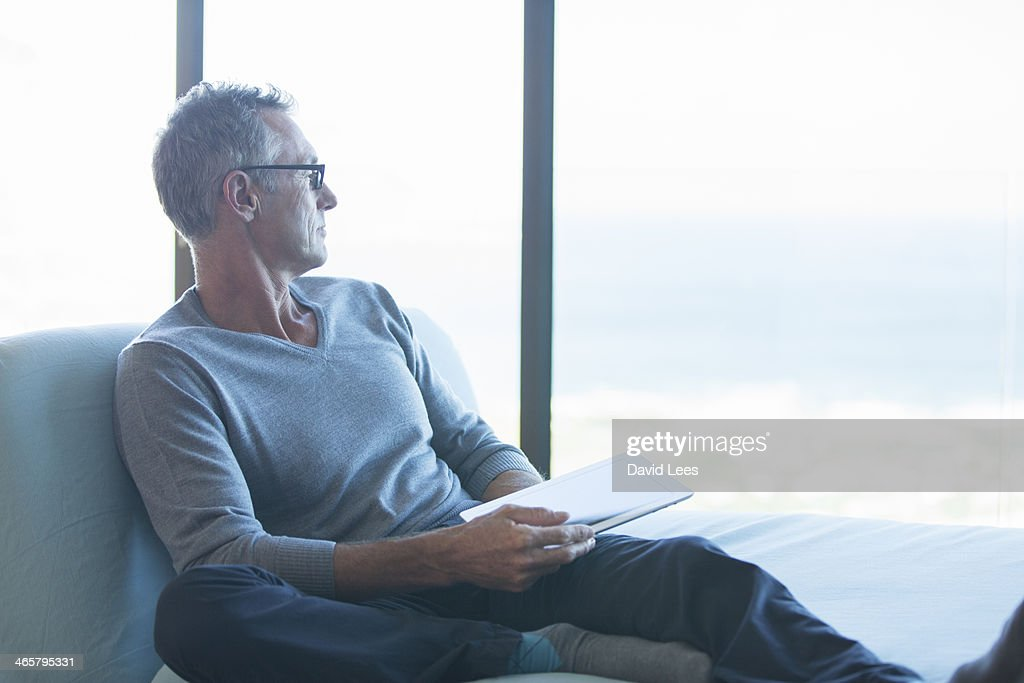 Man sitting by window with digital tablet : Stock Photo