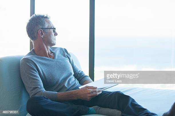 Man sitting by window with digital tablet